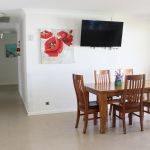 Dining table with 6 chairs tv and artwork on the wall and large hall way